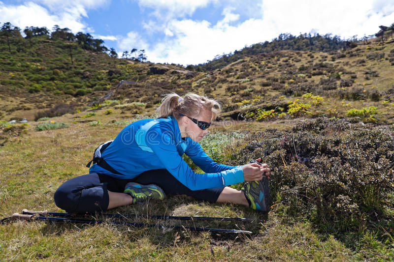 Woman exercising and stretching in mountains royalty free stock photos
