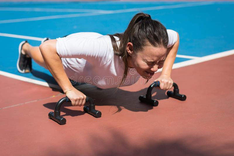A young woman doing pushups outside, exhausted stock image