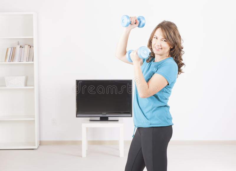 Download Woman exericisng at home stock image. Image of programme - 28074639