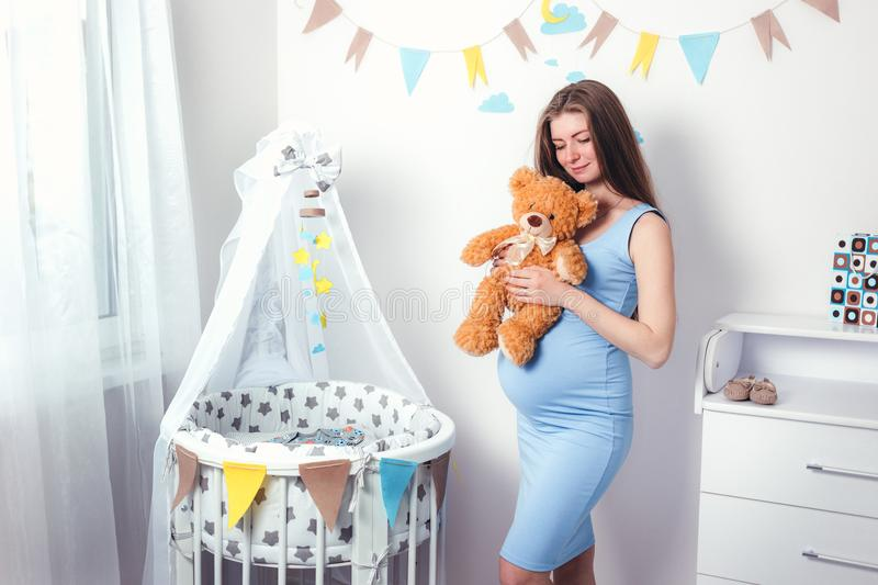 Woman expecting a baby with a brown cute teddy bear royalty free stock image