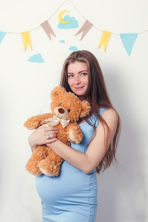 Woman expecting a baby with a brown cute teddy bear stock photos