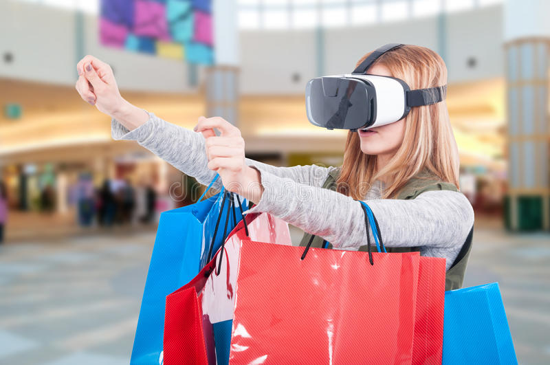Woman experience shopping online with VR headset. Inside the mall stock image