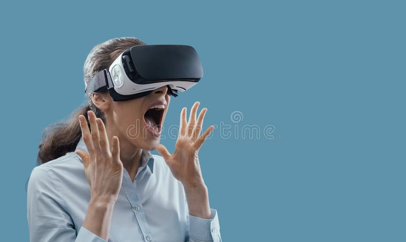 Woman experiencing virtual reality. Woman wearing a VR headset and experiencing virtual reality, she is amazed and surprised stock images