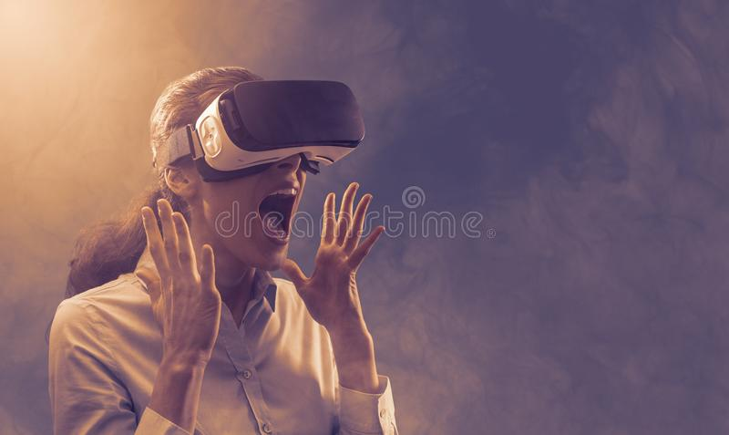 Woman experiencing virtual reality. Woman wearing a VR headset and experiencing virtual reality, she is amazed and surprised stock photo