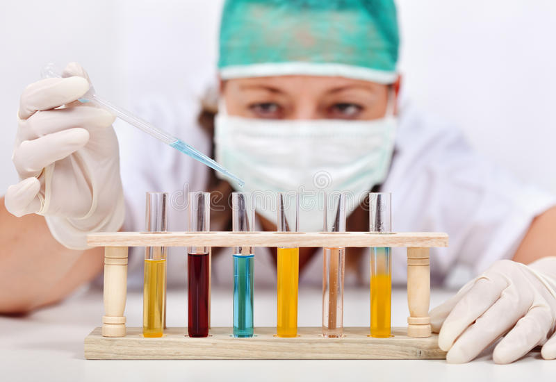 Woman experimenting with various liquids in test-tubes royalty free stock photos