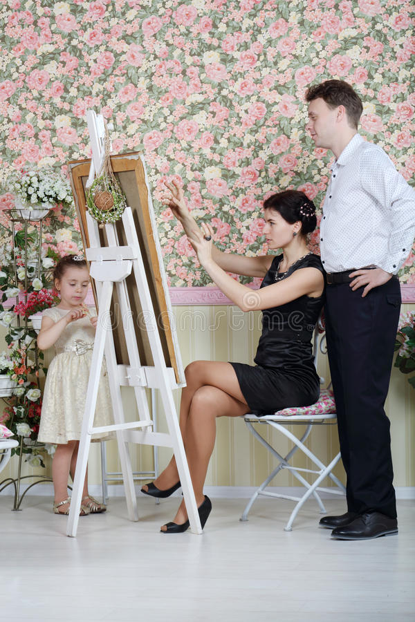 Woman explains her plan to artist and little girl stands. Behind easel in beautiful retro interior royalty free stock photos