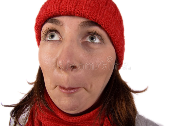 Woman with an Expressive Face!. A young woman wearing a red knit cap and scarf looks up with eyes wide open in amazement and incredulity royalty free stock image
