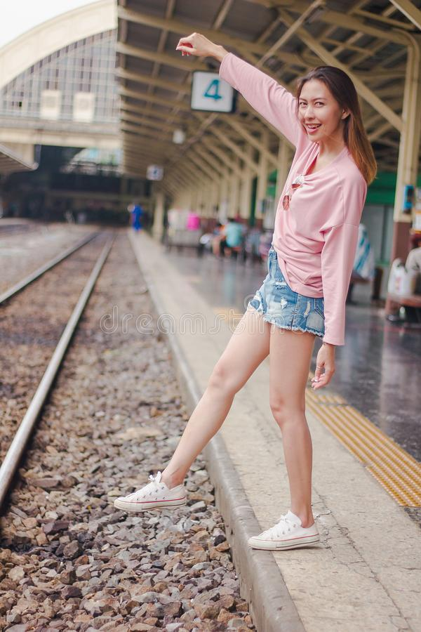 The woman extends her arms to the railroad tracks. royalty free stock photo