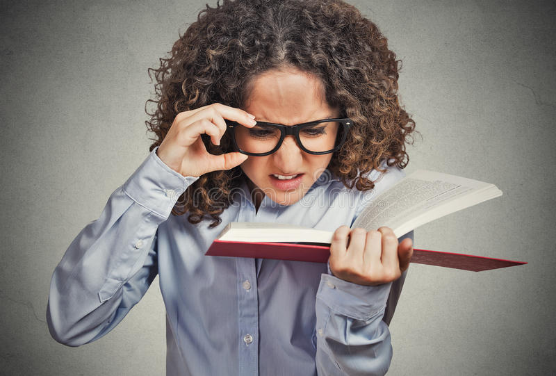 Woman with eye glasses trying to read book, having difficulties seeing text. Closeup portrait young woman with eye glasses trying to read book, having stock photos