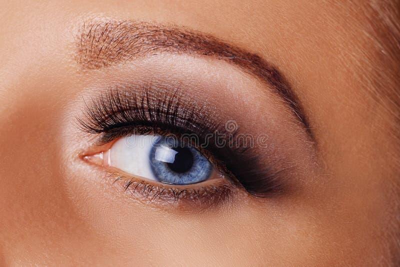 Woman eye with long eyelashes and smokey eyes make-up. Eyelash extensions, makeup, cosmetics, beauty royalty free stock images