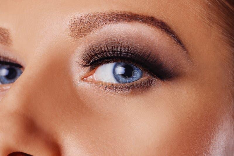 Woman eye with long eyelashes and smokey eyes make-up. Eyelash extensions, makeup, cosmetics, beauty stock photography