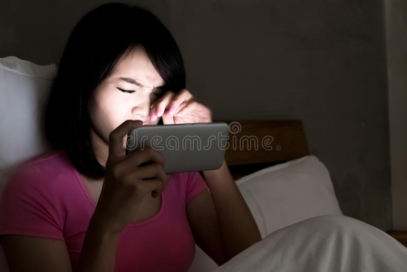 Woman with eye problem. Woman use phone with eye problem on the bed at night stock photo