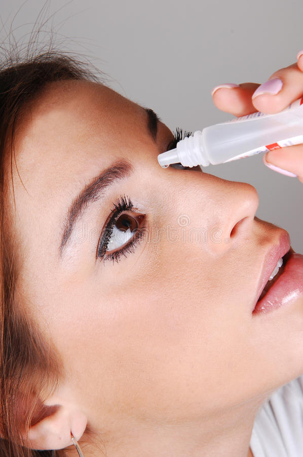 Woman with eyedrops. The face of a young pretty woman putting eye drops in her dry eyes to. get relief for her irritated eyes stock image