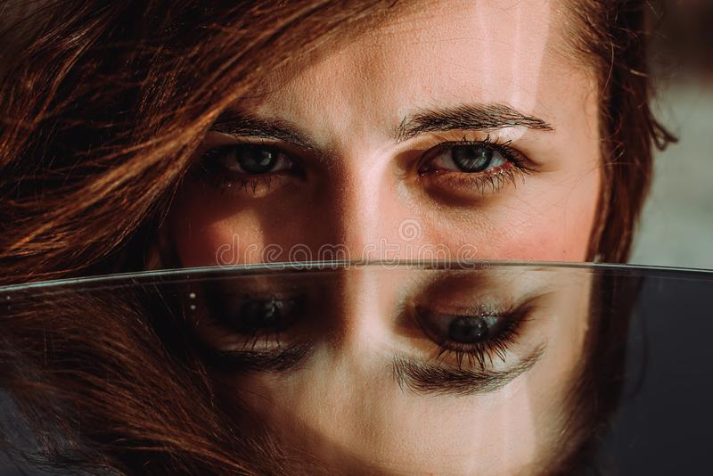 Woman eyes close up reflected in mirror. Hypnotize strong look. Hypnotic deeply penetrating glance. Revengeful insidious expectant. Gaze. Young caucasian girl royalty free stock photos