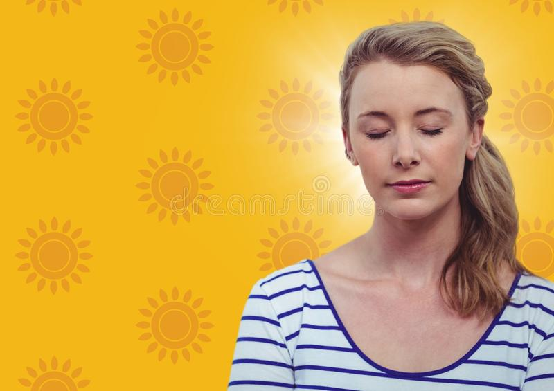 Woman with eyes closed against yellow sun pattern. Digital composite of Woman with eyes closed against yellow sun pattern stock image