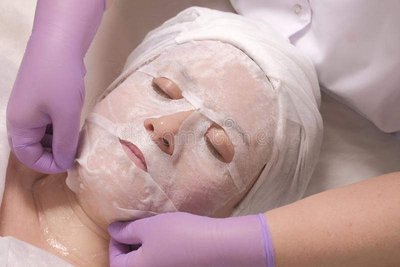 Woman with eyes closed. Hands of the cosmetologist in pink gloves remove the white nourishing mask from the female face. Concept. Woman with eyes closed. Hands stock photos