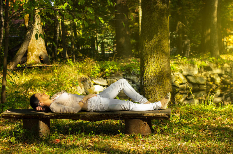 Woman with eyes closed relaxing on a bench in nature royalty free stock image