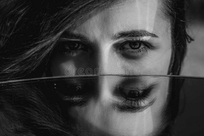 Woman eyes closeup reflected in mirror. Hypnotize strong look. Hypnotic deeply penetrating glance. Revengeful insidious expectant. Gaze. Young caucasian girl royalty free stock photo