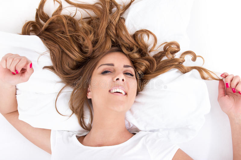 Woman with eyes open and hair spread on bed in bright image. Attractive young woman with eyes open and hair spread on bed in bright image, domestic atmosphere royalty free stock photos