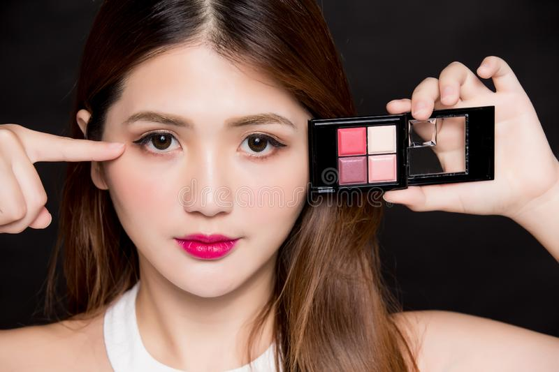 Woman and eyeshadow tray. Woman take eye shadow palette on the black background stock photography
