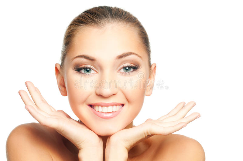 Woman face. Closeup beautiful smiling woman face with hands on white background royalty free stock image