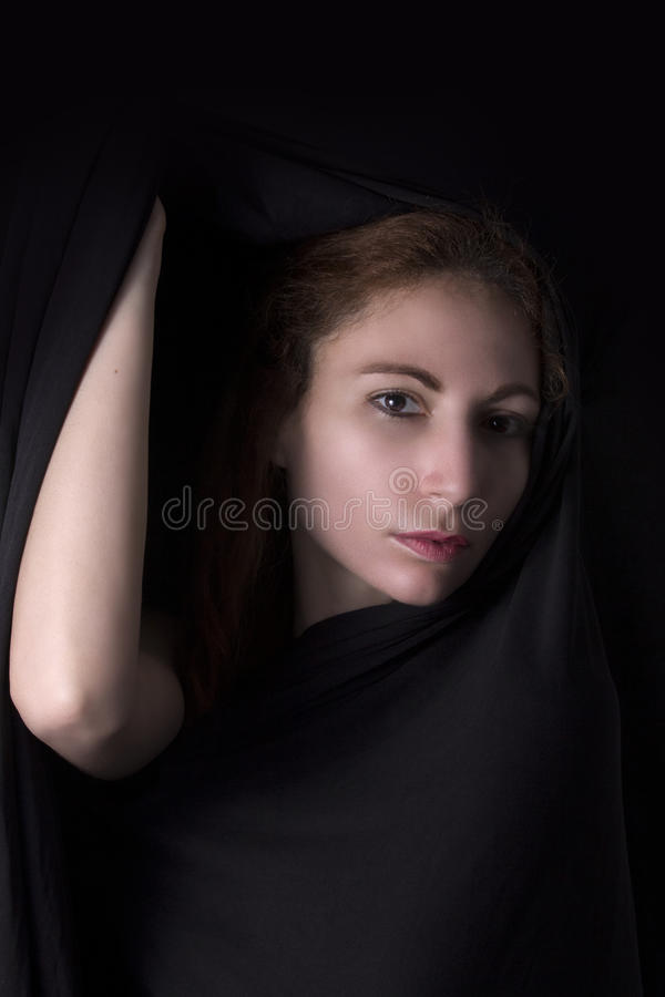 Woman face appear from black background. Woman face and elbow hand appear from black dark background - Beauty portrait stock images