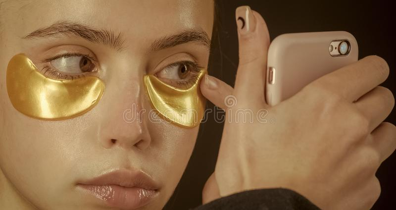 Woman face beauty. skincare, spa, collagen mask under eyes gold color from wrinkles royalty free stock image