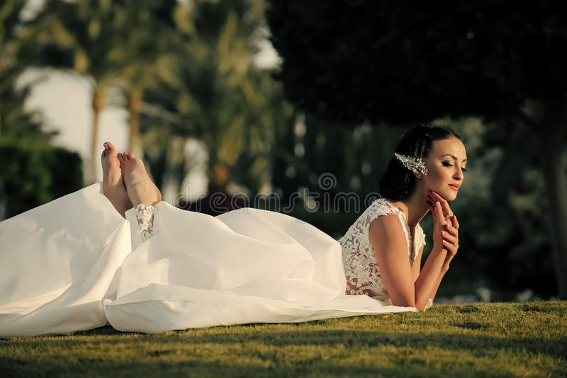 Woman face beauty. Woman lying on green grass on tropical landscape royalty free stock images