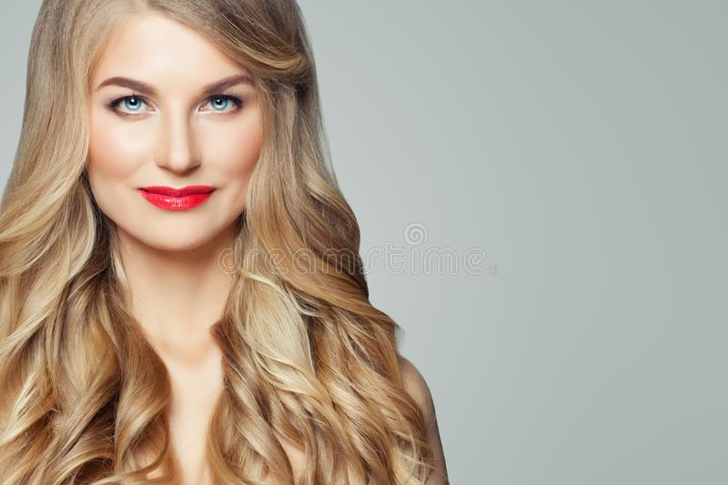 Woman face closeup. Beautiful female model with wavy blonde hairstyle and red lips makeup on background with copy space royalty free stock images