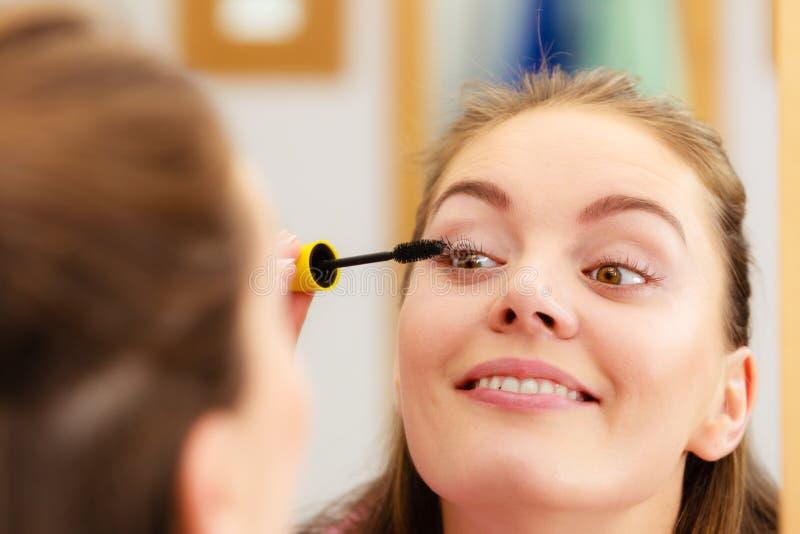 Woman applying black eye mascara to her eyelashes. Woman face eyes painting. Girl applying black eye mascara to her eyelashes looking in bathroom mirror. Makeup royalty free stock photography
