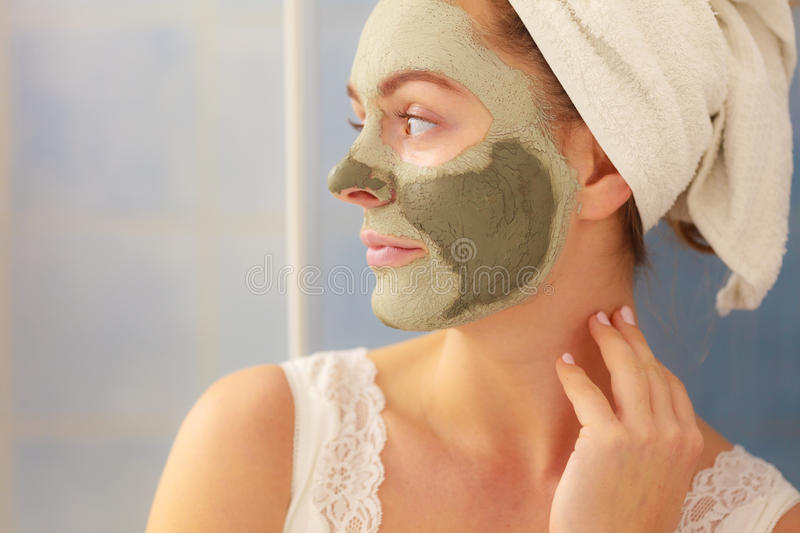 Woman face with green clay mud mask. Skin care. Woman in bathroom with green clay mud mask on face. Girl taking care of oily complexion. Beauty treatment royalty free stock photography