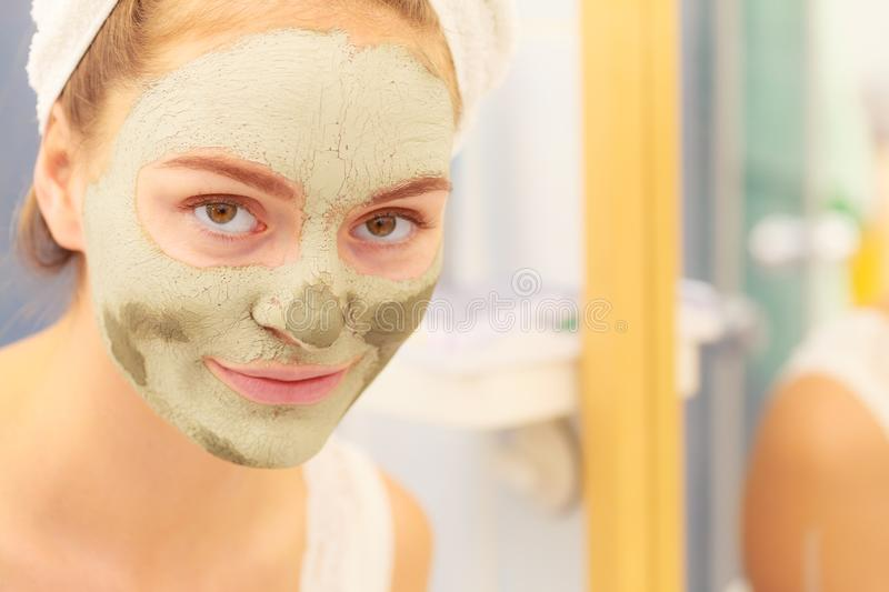 Woman face with green clay mud mask. Skin care. Woman in bathroom with green clay mud mask on face. Girl taking care of oily complexion. Beauty treatment royalty free stock photo