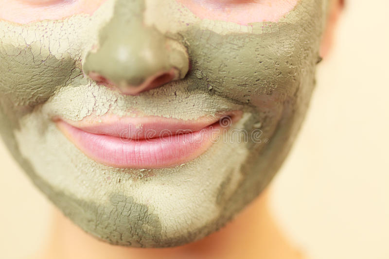 Woman face with green clay mud mask. Skin care. Woman face with green clay mud mask close up. Girl taking care of oily complexion. Beauty treatment stock images