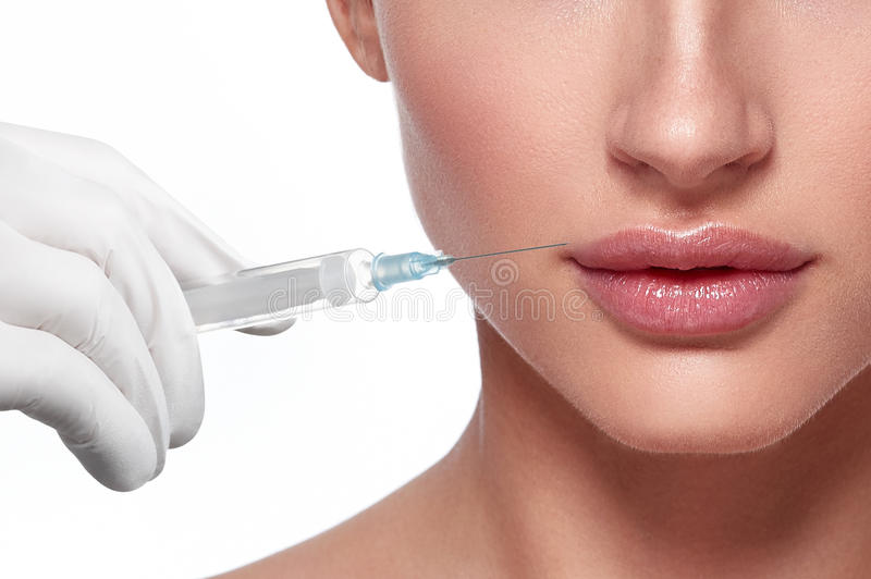 Woman face and hand in glove with syringe making injection. People, cosmetology, plastic surgery and beauty concept - beautiful young woman face and hand in royalty free stock photography