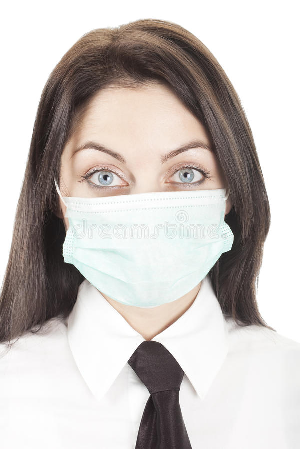 Woman in face mask with big eyes. Young scared businesswoman with black tie wearing green protection face mask isolated on white stock photography