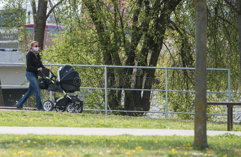 Woman with face mask carring baby-carriage in the park royalty free stock photo