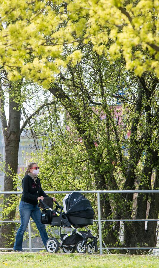 Woman with face mask carring baby-carriage in the park stock image
