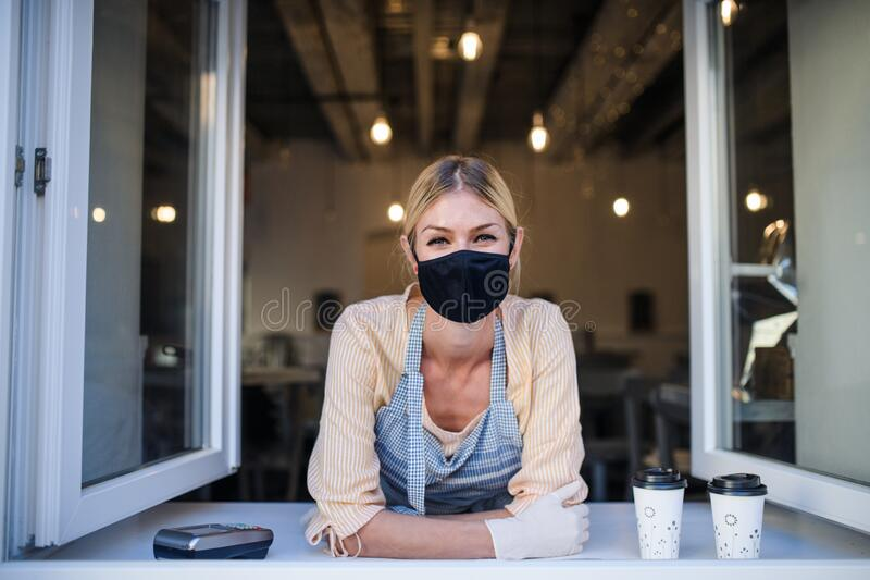 Woman with face mask serving coffee through window, shop open after lockdown. stock photography