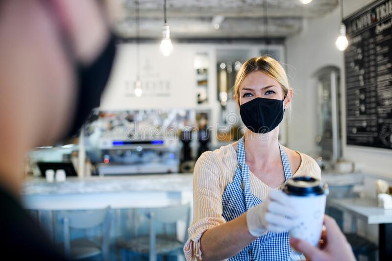 Woman with face mask serving customer, shop open after lockdown quarantine. stock images