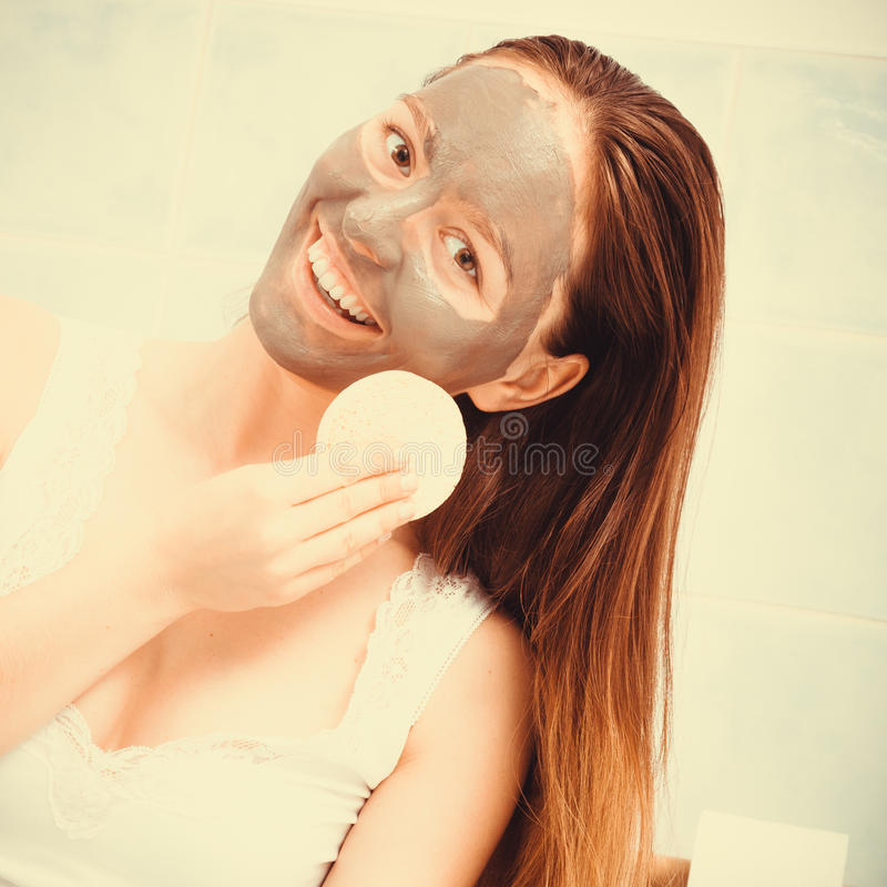 Woman face with mud facial mask. Beauty procedures spa and skin care concept. Young woman with facial clay mask in bathroom holds sponge to remove mud stock photography