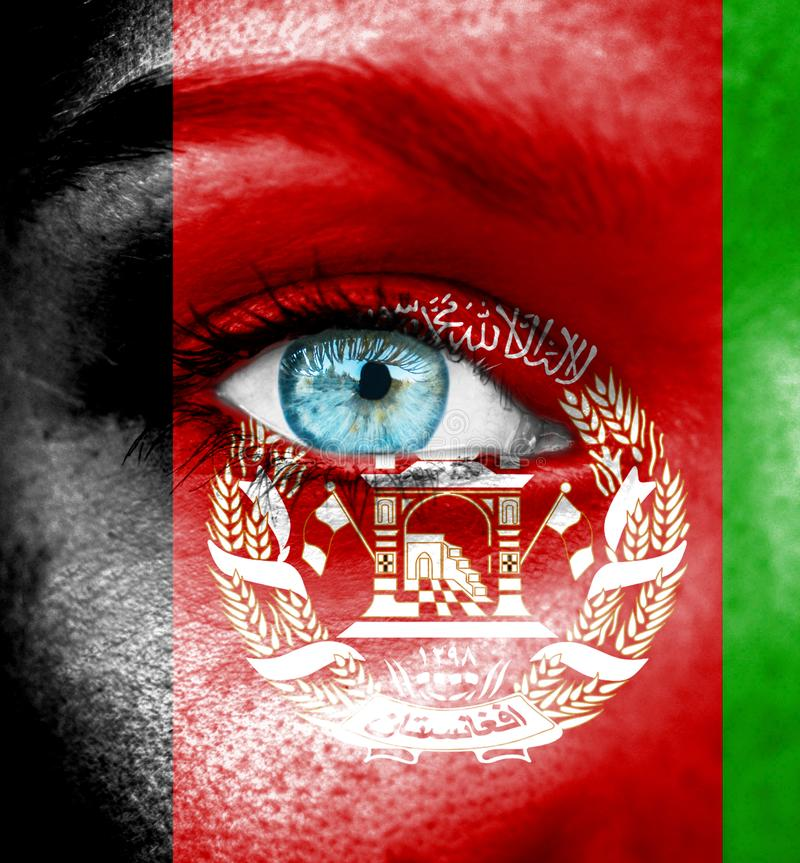 Woman face painted with flag of Afghanistan stock photo
