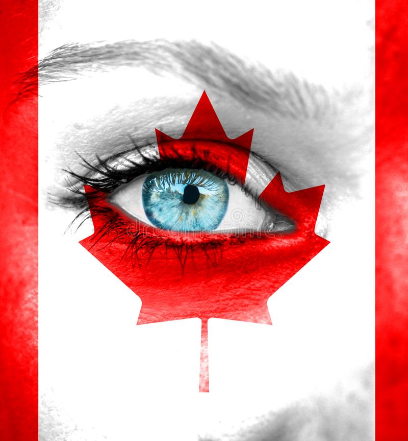 Woman face painted with flag of Canada stock photography