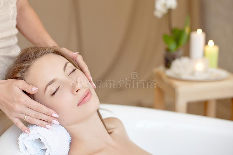 Woman face with perfect skin doing facial massage in a bathtub royalty free stock photo