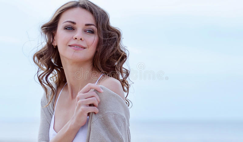 Woman face Portrait on the beach. Happy beautiful curly-haired girl close-up, the wind fluttering hair. Spring portrait on the bea royalty free stock image