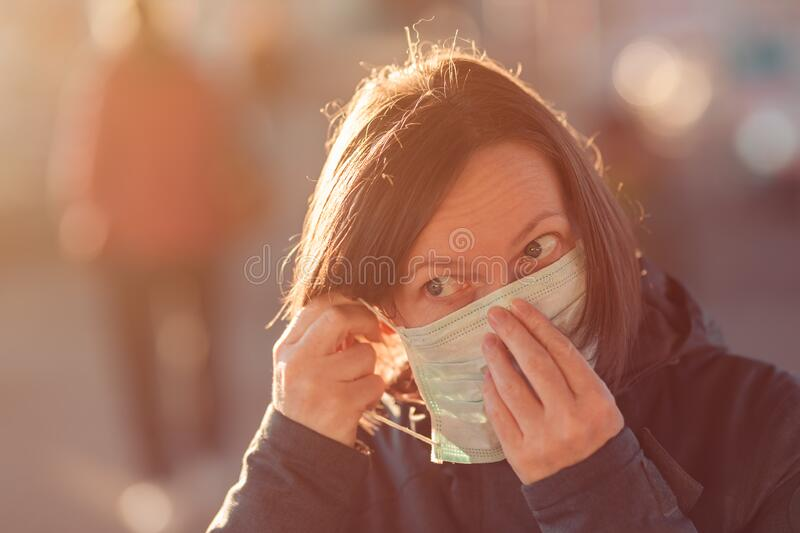 Woman with face protective mask standing on the street royalty free stock photo