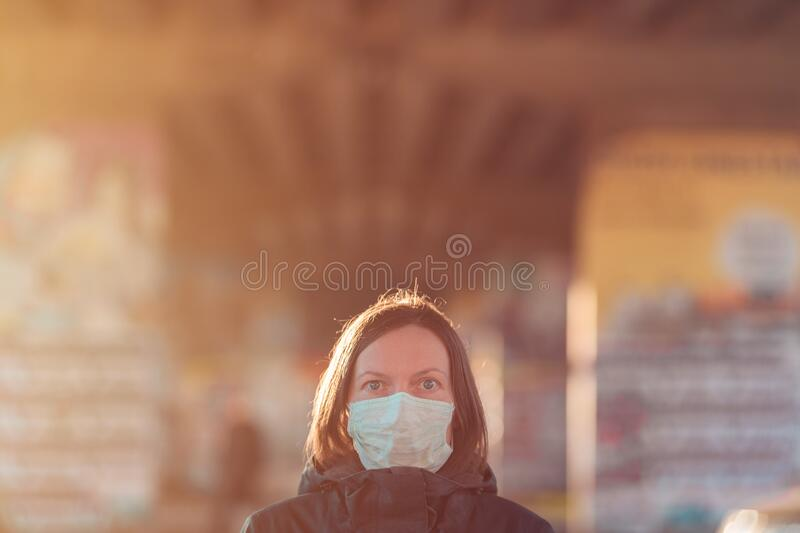 Woman with face protective mask standing on the street royalty free stock image
