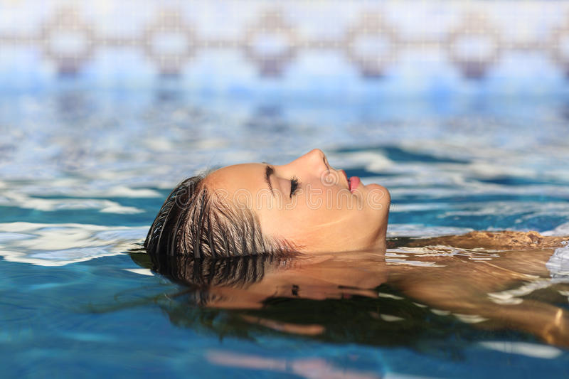 Woman face relaxing floating on water of a pool or spa. Side view of a woman face relaxing floating on water of a swimming pool or spa