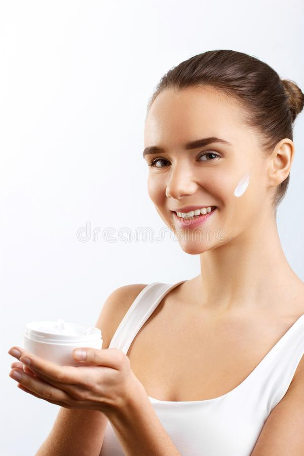 Skincare. Beauty Concept. Young Pretty Woman Holding Cosmetic Cream.Girl wiht fresh skin,. Woman Face Skin Care. Portrait Of Attractive Young Female Applying stock photo
