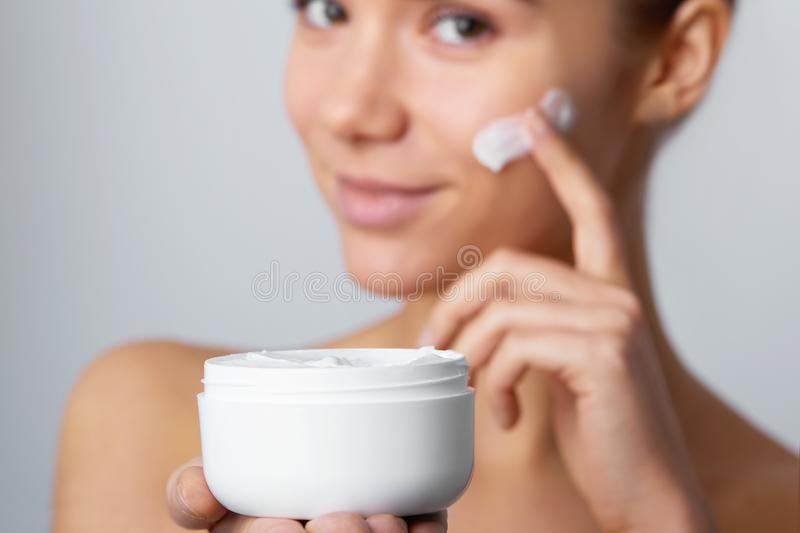 Woman Face Skin Care. Portrait Of Attractive Young Female Applying Cream And Holding Bottle. royalty free stock photos