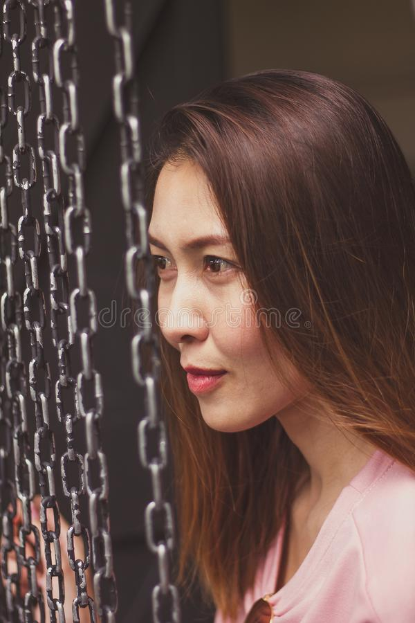 Woman face with steel chain. The woman`s face is close to the black steel chain hanging royalty free stock photography